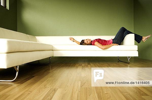Junge Frau auf dem Sofa liegend