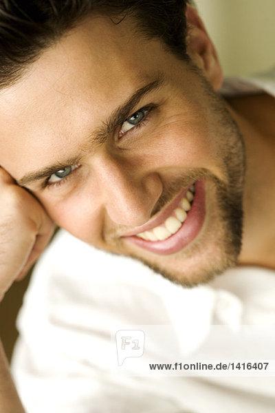 Porträt eines jungen Mannes  der für die Kamera lächelt