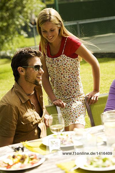 Junges lächelndes Paar am Gartentisch