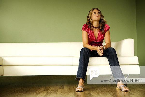 Junge denkende Frau auf einem Sofa sitzend