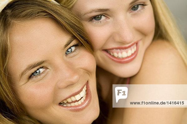Porträt von 2 jungen Frauen  die für die Kamera lächeln