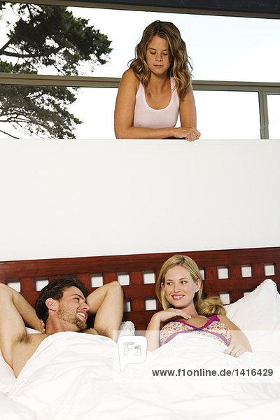 Junge Frau beobachtet junges Paar im Bett