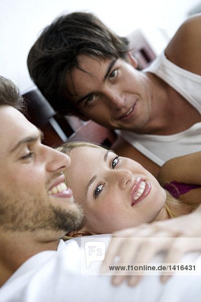 2 lächelnde Männer und eine Frau im Bett liegend