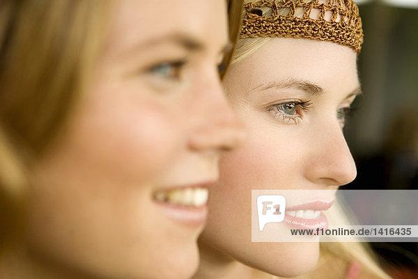 Portrait von 2 jungen lächelnden Frauen  Ansicht im Profil