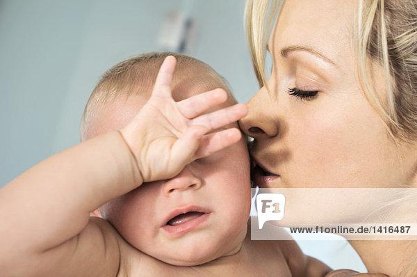 Porträt einer Mutter  die ihr Baby küsst  drinnen