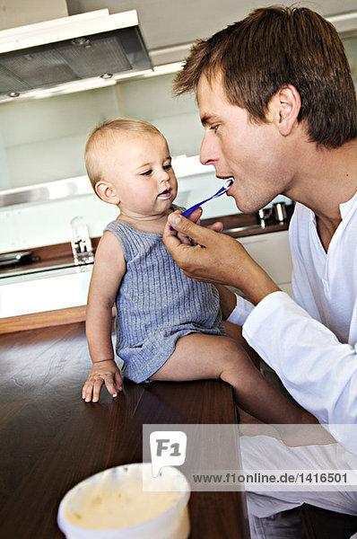 Vater und Baby in der Küche  Mann füttert seinen Sohn  drinnen