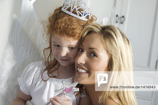 Weihnachtsfeiertag  Porträt einer lächelnden Mutter und Tochter  Blick in die Kamera  drinnen
