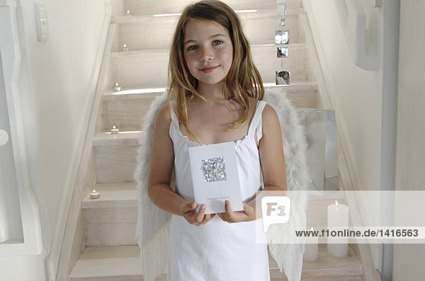 Little girl in an angel costume  holding a Christmas card  indoors