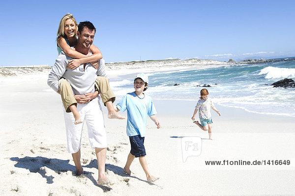 Eltern und zwei Kinder laufen am Strand  Mann trägt Frau auf dem Rücken  im Freien