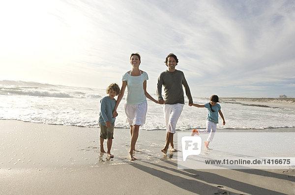Paar  Sohn und Tochter gehen am Strand spazieren  im Freien