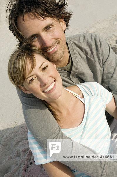 Porträt eines Paares  das am Strand lächelt  für die Kamera posiert  im Freien