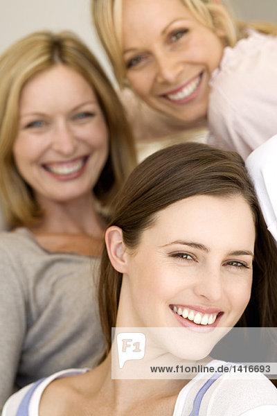 Drei Frauen lächeln für die Kamera  drinnen