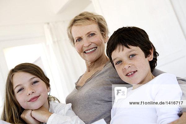 Seniorin und drei Kinder mit Blick auf die Kamera  drinnen