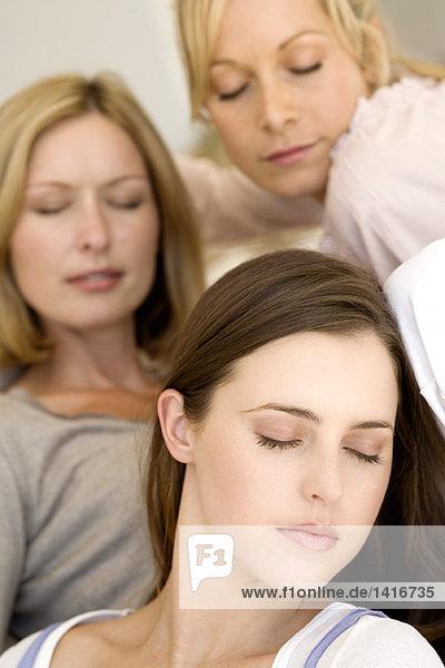 Drei Frauen mit geschlossenen Augen  drinnen