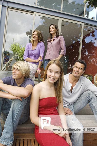 Eltern und drei Teenager vor dem Haus  drinnen