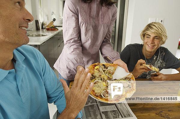Eltern und Teenager essen Pizza  drinnen