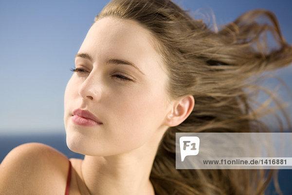 Porträt einer jungen Frau  die wegschaut  Wind im Haar  im Freien