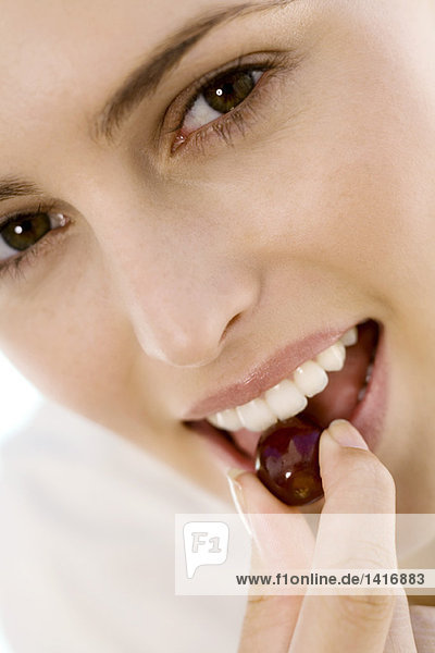 Porträt einer jungen Frau  die eine Kirsche isst  drinnen