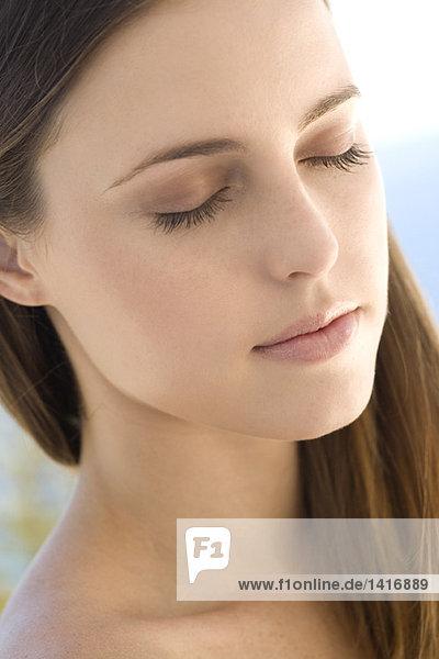 Porträt einer jungen Frau  geschlossene Augen  drinnen
