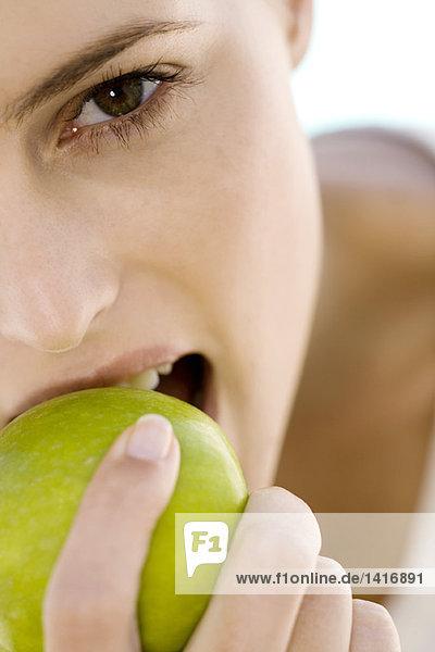 Porträt einer jungen Frau  die einen Apfel isst  drinnen