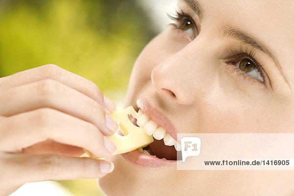Porträt einer jungen Frau  die ein Stück Greyerzer Käse isst  im Freien