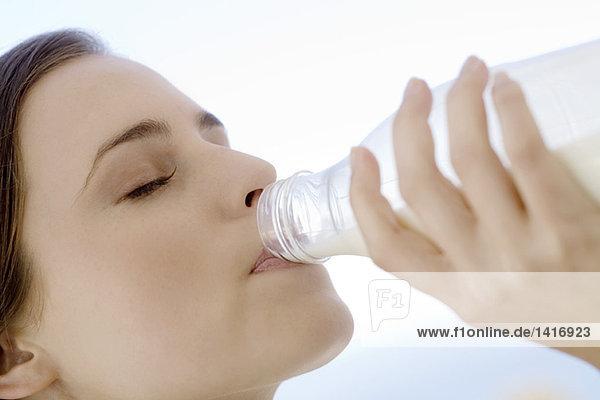 Porträt einer jungen Frau  die Milch aus der Flasche trinkt  im Freien