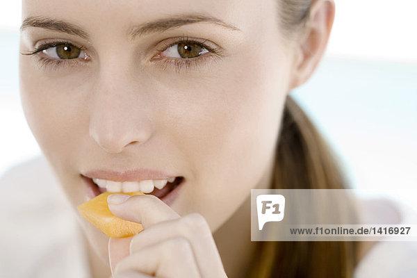 Porträt einer jungen Frau  die ein Stück Melone isst  drinnen