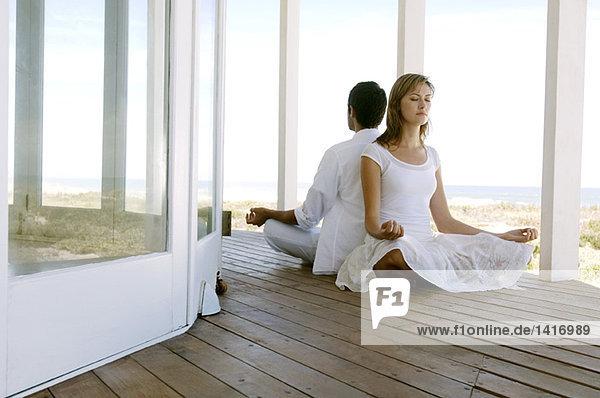 Junges Paar in Yoga-Haltung  draußen