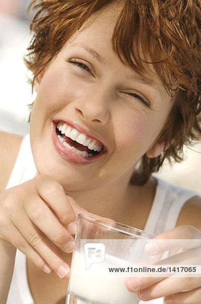 Porträt einer jungen lächelnden Frau mit einem Glas Milch