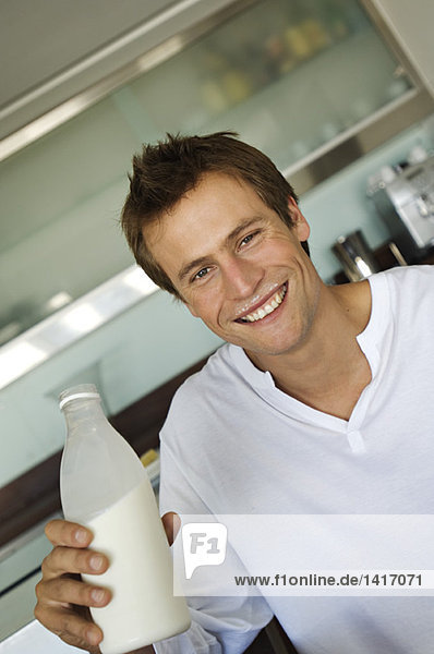 Portrait of a young smiling man holding bottle of milk