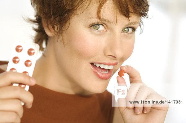 Porträt einer jungen lächelnden Frau mit Pillen