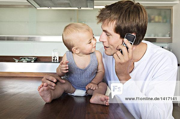 Junger Mann ruft an  umarmt Baby