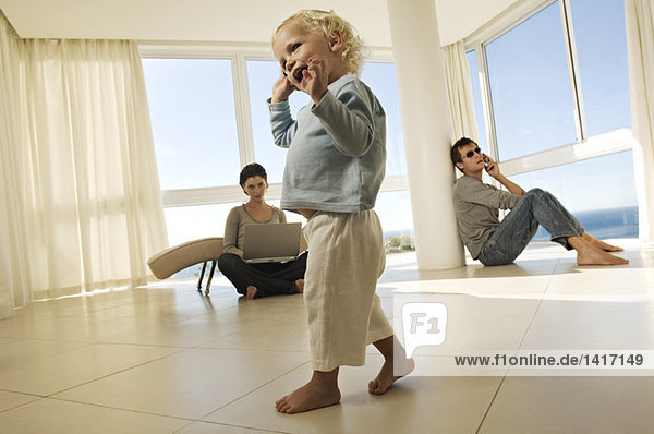 Kleines Mädchen mit Handy  Eltern im Hintergrund