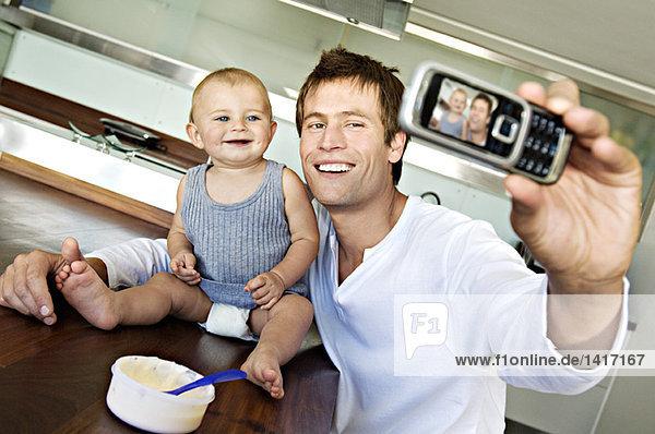Junger Mann mit Baby  mit Fotohandy