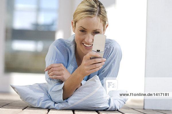 Junge Frau auf dem Boden liegend  mit Handy