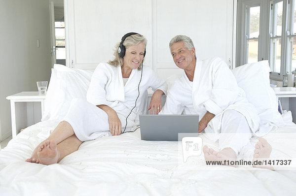 Paar im Bademantel mit Laptop im Bett