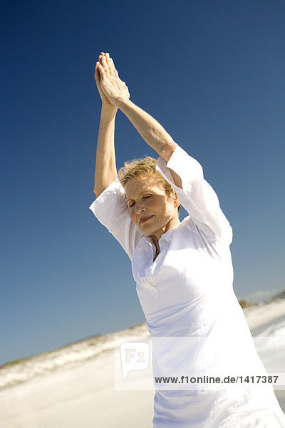 Seniorin beim Yoga am Strand