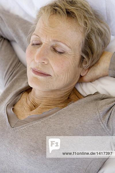 Seniorin schlafend  Hände hinter dem Kopf