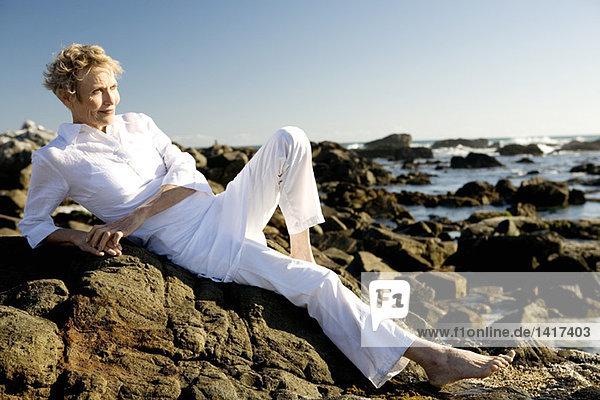 Seniorin auf Felsen am Meer liegend