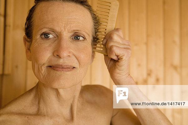 Porträt einer älteren Frau  die ihr Haar kämmt