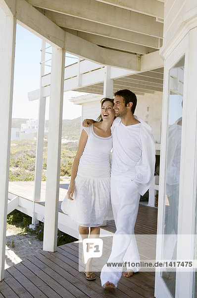 Smiling couple embracing  walking on wooden terrace