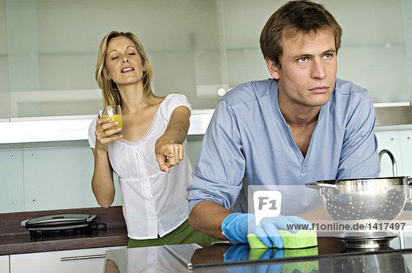 Lächelnde Frau  die auf einen wütenden Mann zeigt  der einen Schwamm hält.