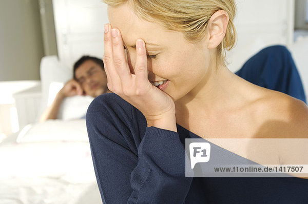 Porträt einer lachenden jungen Frau  die den Mund bedeckt  schmollender Mann im Bett liegend im Hintergrund