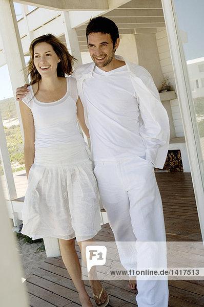 Lächelndes Paar umarmend  auf Holzterrasse spazierend