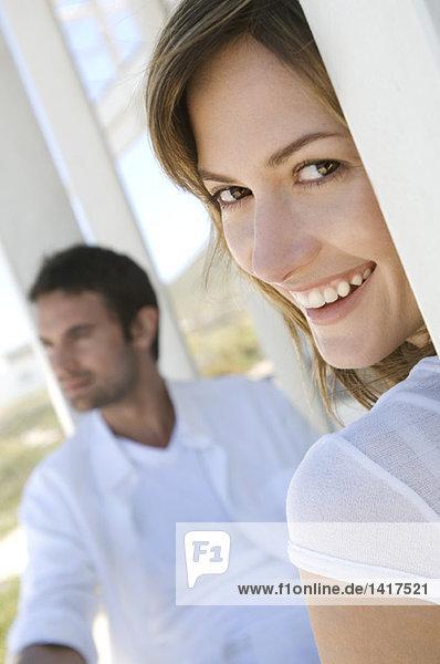 Paar auf der Terrasse  Frau lächelt für die Kamera im Vordergrund