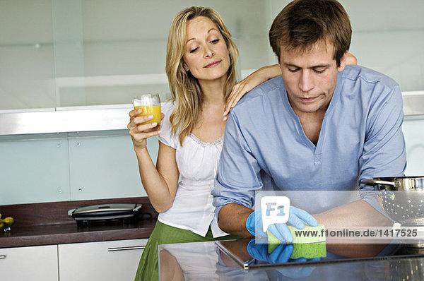 Junge Frau lacht über Mann mit Schwamm in der Küche