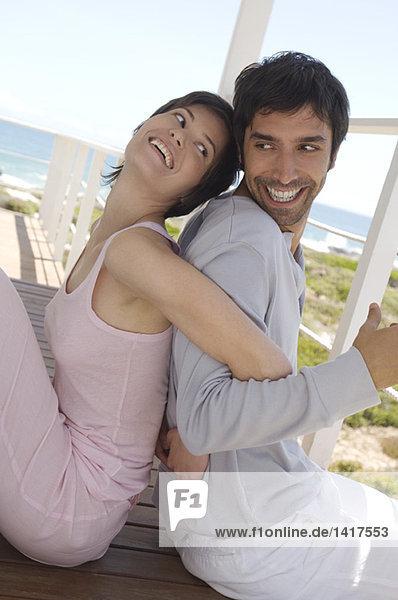 Lächelndes Paar sitzend  Rücken an Rücken  auf Holzterrasse