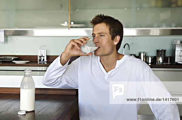 Junger Mann trinkt Milch in der Küche