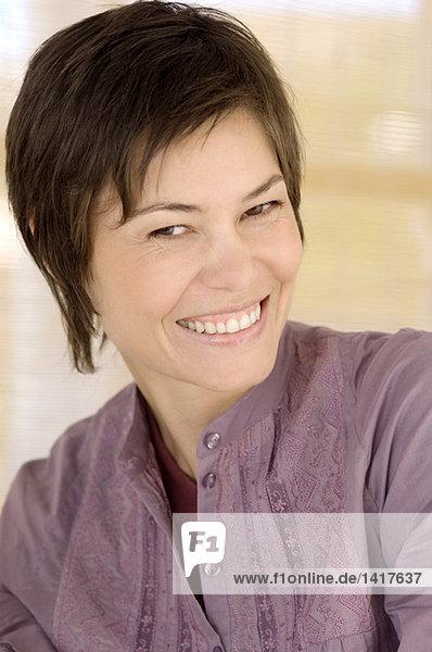 Porträt einer jungen Frau  die für die Kamera lächelt