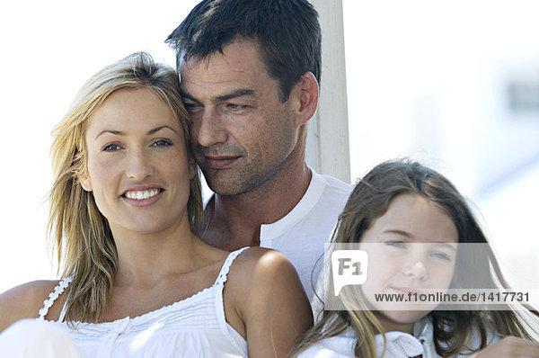 Eltern und Tochter lächeln für die Kamera  im Freien